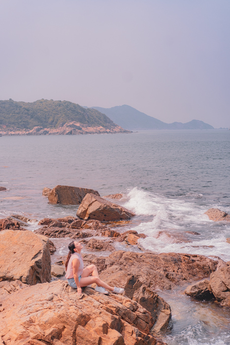 A girl sitting on the beach shore in Tap Mun