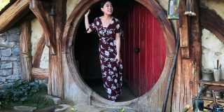 A girl of East Asian descent posing in front of a hobbit hole in Hobbiton New Zealand